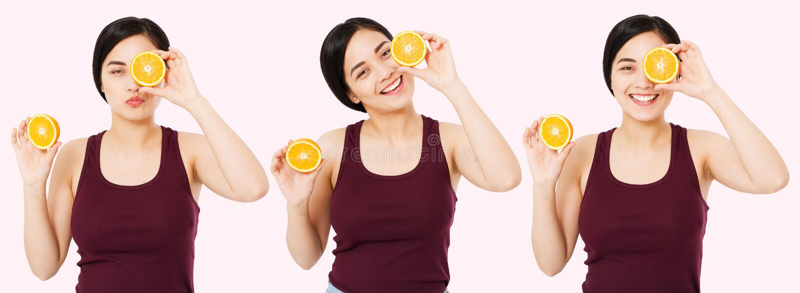 Установленный счастливый азиат, китайская женщина с хорошей кожей держа половины апельсина около стороны, концепцию skincare крас стоковые изображения