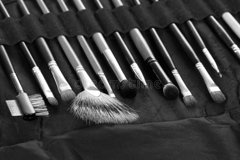 Установленные профессиональные щетки косметики в черной предпосылке случая стоковая фотография