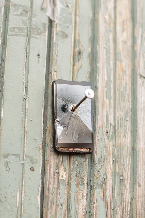 Устарелый мобильный телефон пригвозжен к деревянной загородке стоковая фотография rf