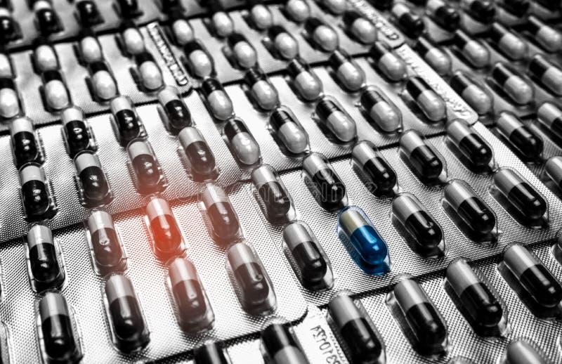 Устойчивость к лекарственному средству антибиотиков Сине-белая пилюлька капсулы стоя вне от толпы черно-белых пилюлек капсулы Рук стоковая фотография