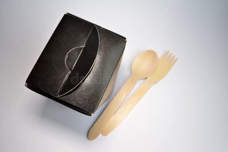 Устранимый черный квадратный пищевой контейнер картона на вынос на белой предпосылке, рядом с ним лежит деревянные ложка и вилка стоковое изображение