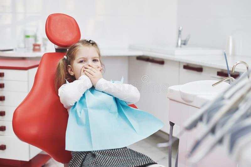 Устрашенная маленькая девочка на офисе дантиста предусматривала рот с руками стоковая фотография rf