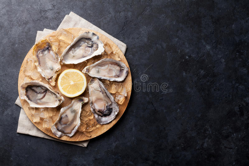 Устрицы и лимон над льдом стоковая фотография