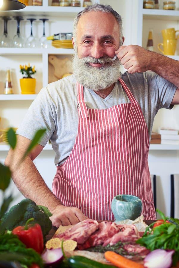 Услаженный усик старшего человека вертясь пока подготавливающ мясо dis стоковое изображение rf