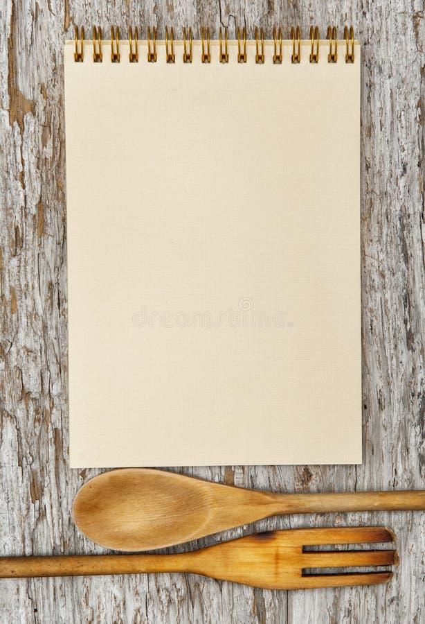 Утвари кухни и бумажная спиральная тетрадь на старой древесине стоковая фотография rf