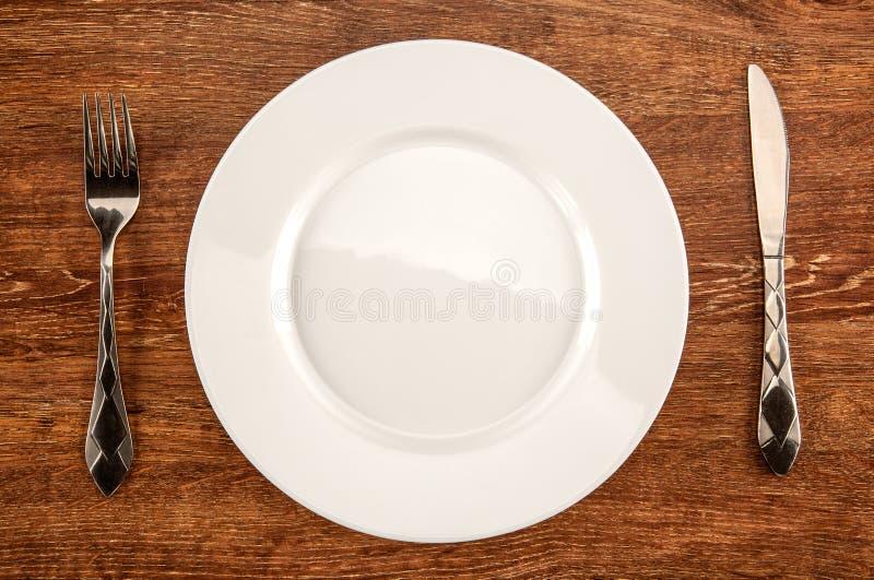 Утвари Kitchenware в форме белых плиты, вилки и kni стоковое изображение