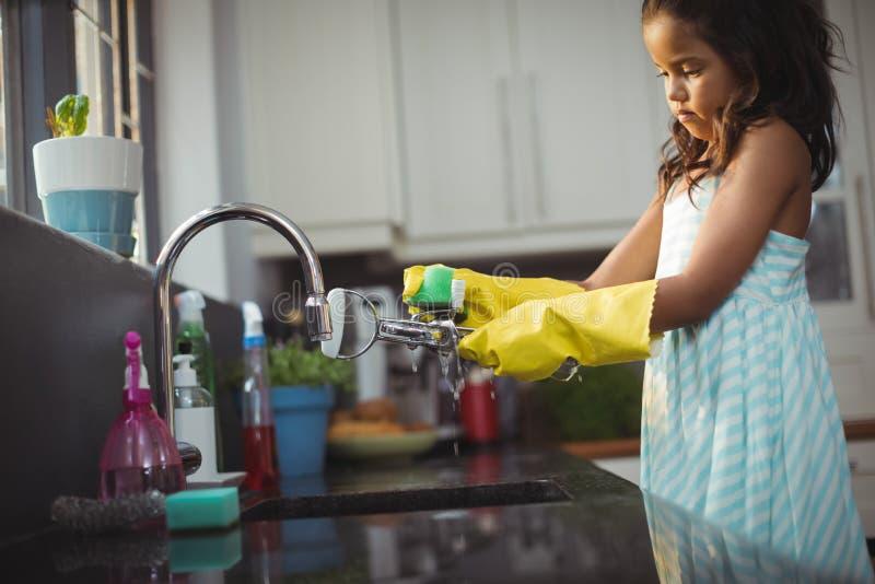 Утварь милой маленькой девочки моя в кухонной раковине стоковое фото