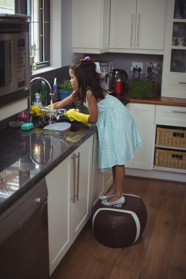 Утварь милой маленькой девочки моя в кухонной раковине стоковые фотографии rf