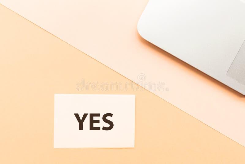 Утвердительный ответ и ноутбук слова на оранжевой предпосылке Творческая концепция канцлерского суда минимализма Взгляд сверху, п стоковое изображение rf