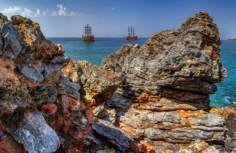 Утесы горы Seascape и голубое море с кораблями на горизонте Скалистые камни на турецком пляже в Alanya, Турции стоковые фотографии rf