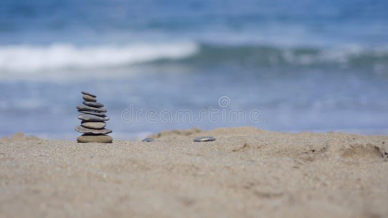 Утесы и песок на предпосылке океана стоковые изображения