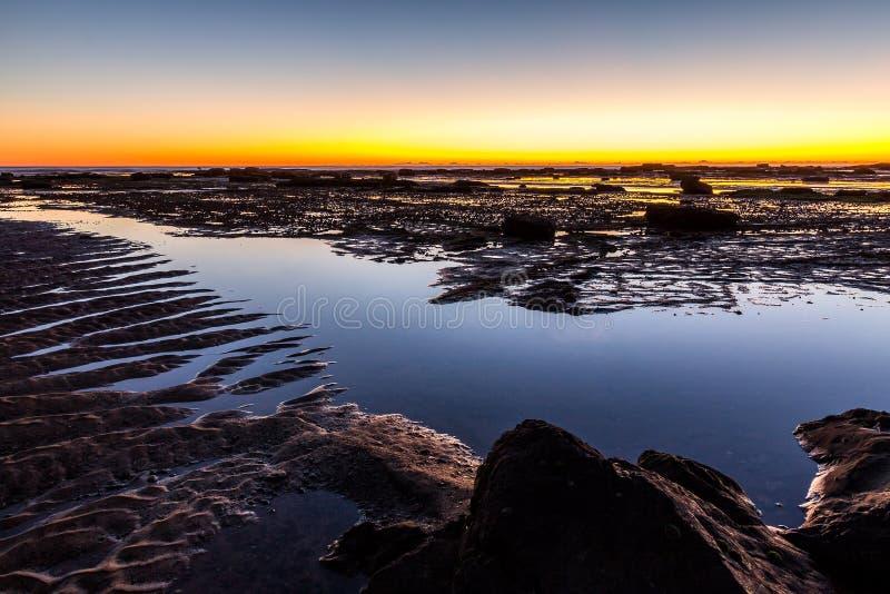 Утесы на длинном пляже рифа на зоре стоковые изображения