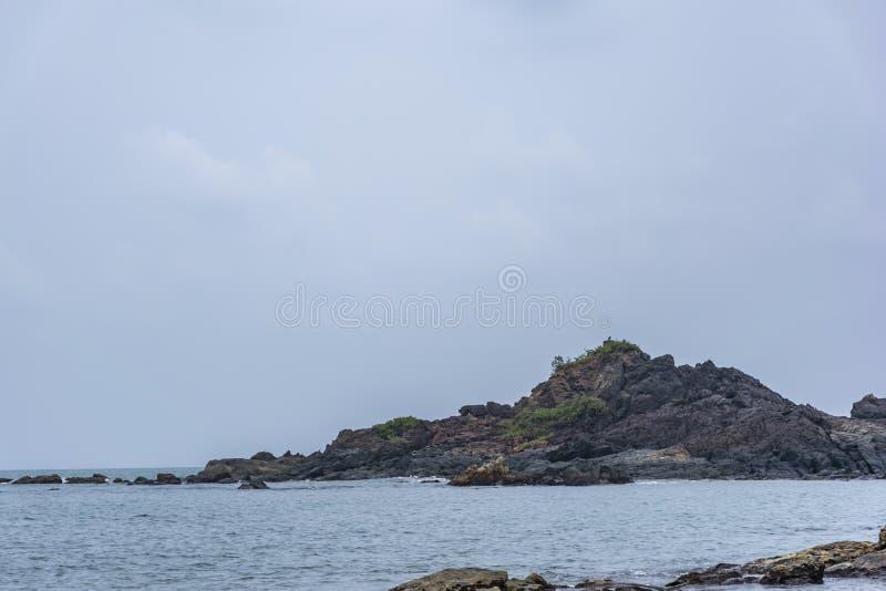 Утесы на пляже смотря на волны - Gokarna стоковая фотография rf