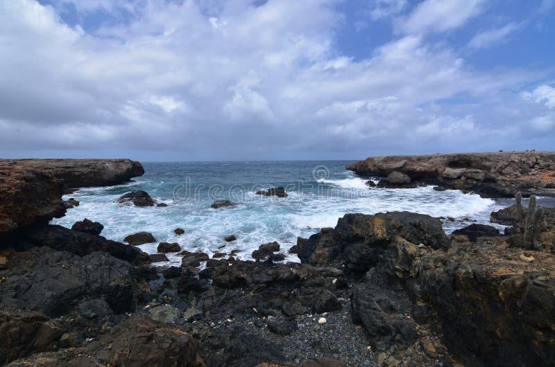 Утес лавы окружая бухту на береговой линии ` s Аруба восточной стоковые фотографии rf