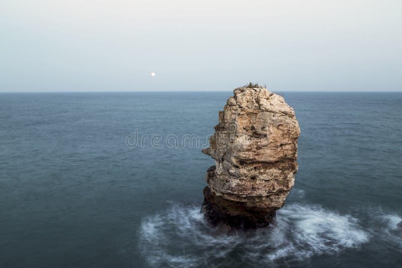 Утес в море и поднимая луне стоковое изображение