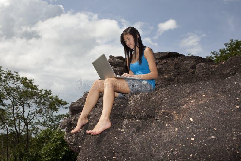 утес компьтер-книжки сидит подросток стоковая фотография