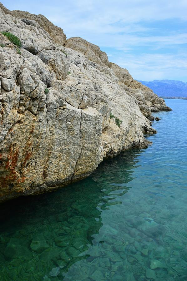 Утес крутого бечевника sundried около лазурной бухты в немножко пасмурном после полудня около Vrsi, Хорватии стоковые фото