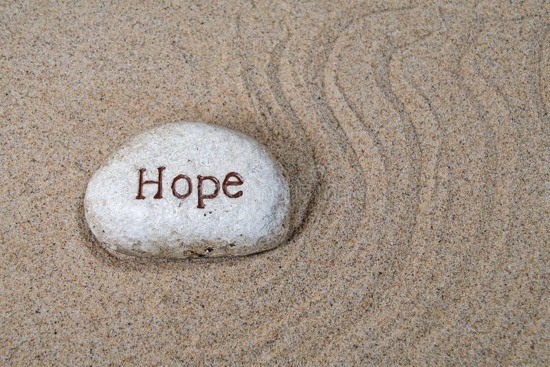 Утес надежды в песке пляжа стоковые фото