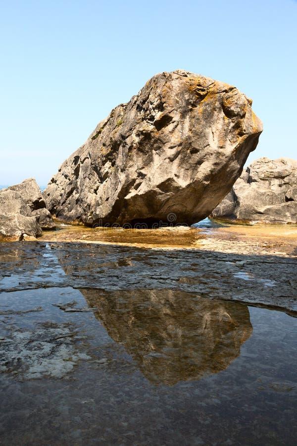 Download Утес отраженный в воде стоковое изображение. изображение насчитывающей отражение - 33734837