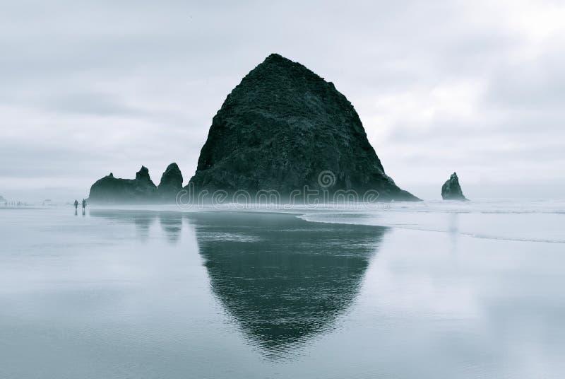 Утес стога сена во время отлива под серыми небесами стоковое изображение