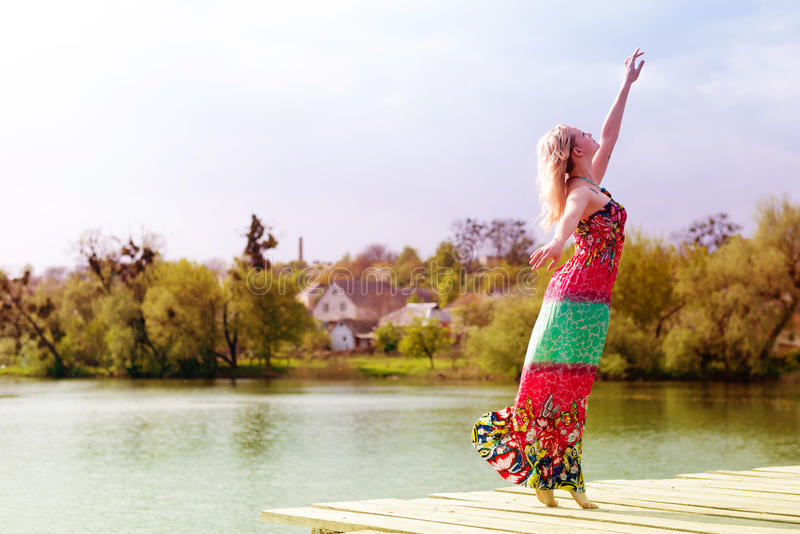 Утеха танцев: красивые белокурые детеныши уменьшают женщину наслаждаясь протягивать в длинном светлом платье на озере воды на зел стоковая фотография