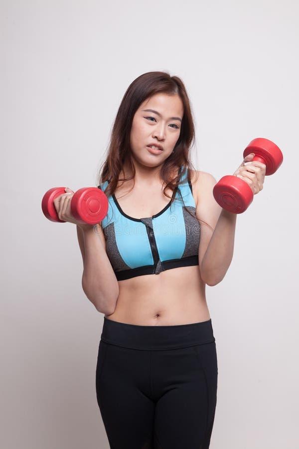 Утомленная азиатская здоровая тренировка девушки с гантелью стоковое изображение rf