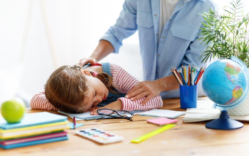 Утомленная девушка ребенка упала уснувший когда она сделала ее домашнюю работу дома стоковые фотографии rf