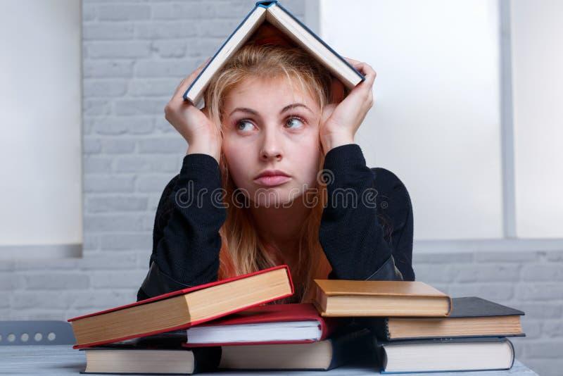 Утомленная девушка, сидит рядом с кучей книг и держит книгу надземный учить принципиальной схемы стоковое фото rf