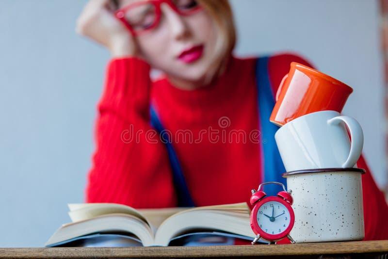 Утомленная девушка с чашками кофе и книгами стоковое фото rf