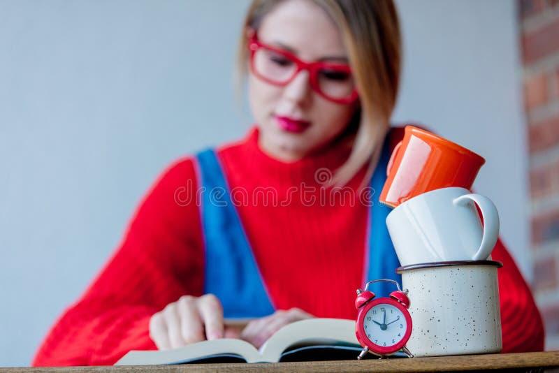 Утомленная девушка с чашками кофе и книгами стоковое изображение rf