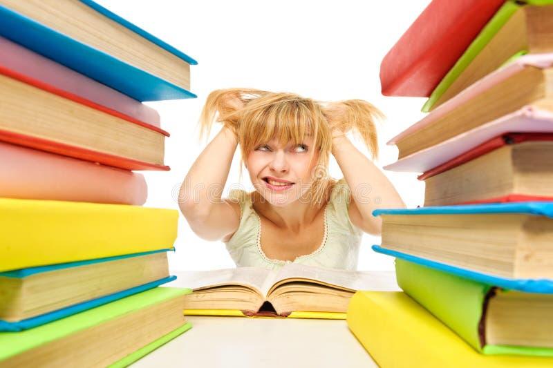 Утомленная женщина сидя на столе окруженном с кучами книг стоковое изображение rf