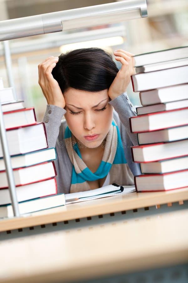 Утомленная красивейшая женщина окруженная с книгами стоковые фотографии rf