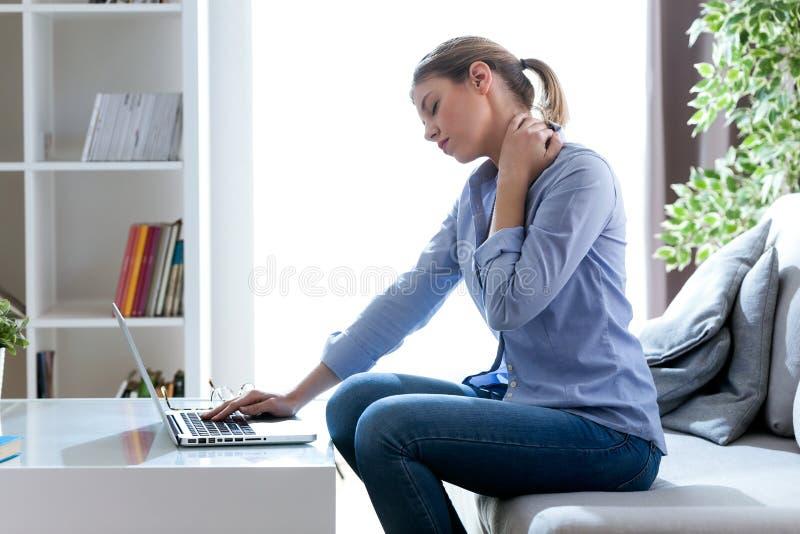 Утомленная молодая женщина с болью шеи используя ее компьтер-книжку дома стоковое изображение