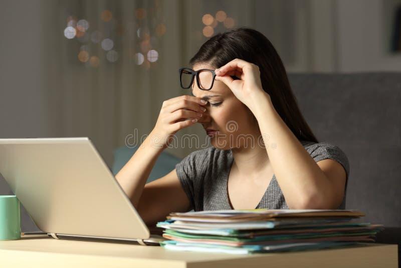 Утомленные работающий на самого себя касаясь глаза работая последние часы стоковое изображение