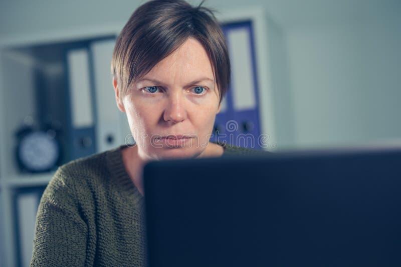 Утомленный вымотанный женский фрилансер работая на портативном компьютере стоковое изображение