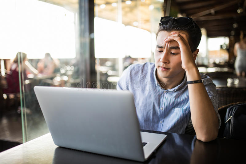 Утомленный вымотанный молодой азиатский мужчина работая с компьтер-книжкой в кафе Работать работа стоковое изображение
