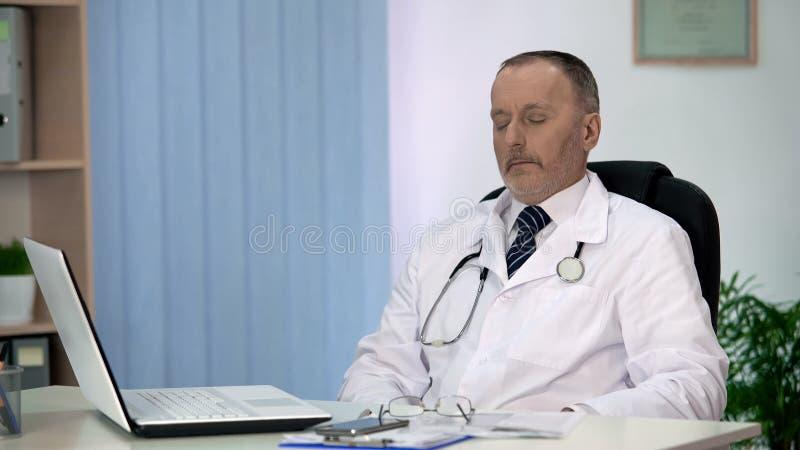 Утомленный главный врач ослабляя после выматывать рабочий день, напряжённую работу стоковое фото rf