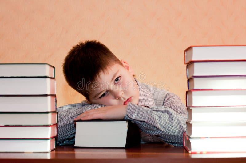 Утомленный малыш с стогом книг стоковое изображение