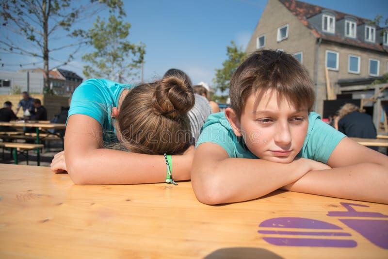 Утомленный мальчик и девушка сидя с руками на его стороне стоковая фотография