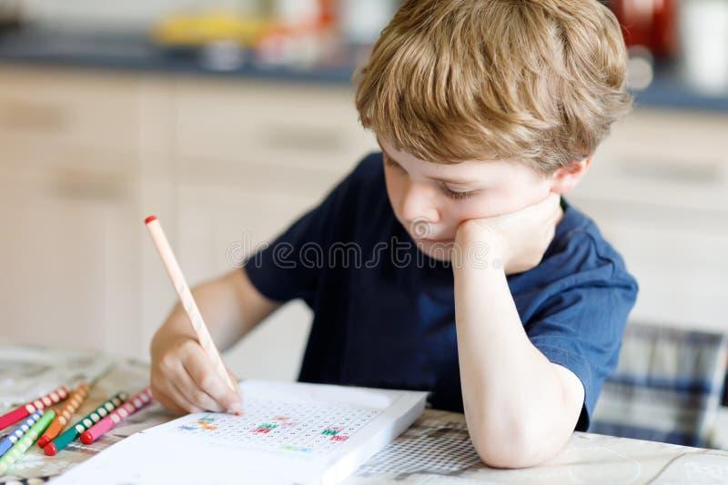 Утомленный мальчик ребенк дома делая письма сочинительства домашней работы с красочными ручками стоковые изображения rf