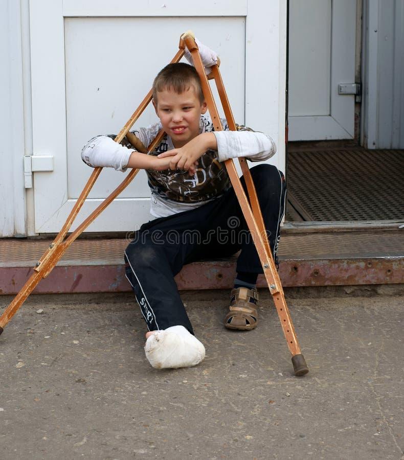 Утомленный мальчик с сломанной ногой и деревянными костылями внешними стоковые изображения rf