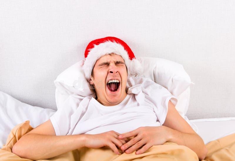 Утомленный молодой человек в шляпе Санты стоковые изображения