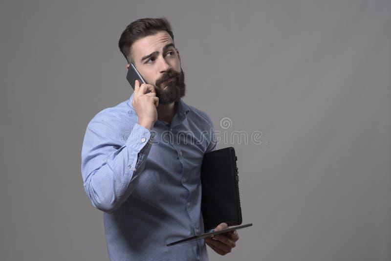 Утомленный перегружанный человек на телефоне держа компьтер-книжку и планшет смотря прочь стоковое фото rf