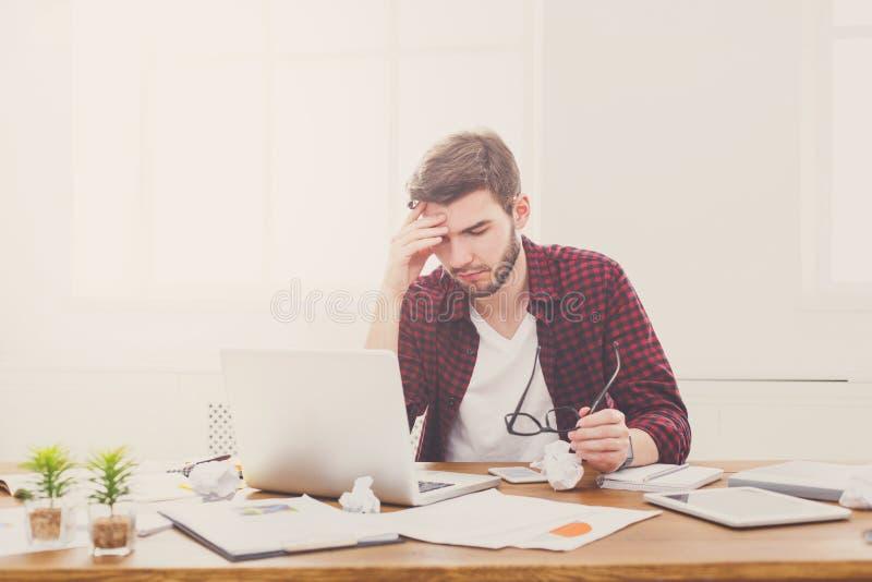 Утомленный, перегружающ бизнесмена с компьтер-книжкой в современном белом офисе стоковые фото