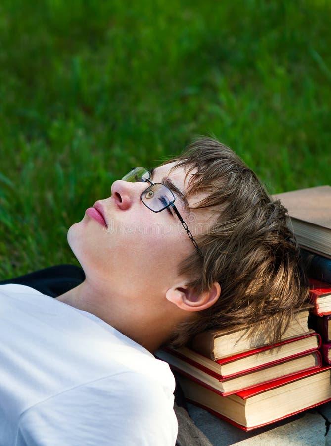 Утомленный подросток с книги стоковая фотография