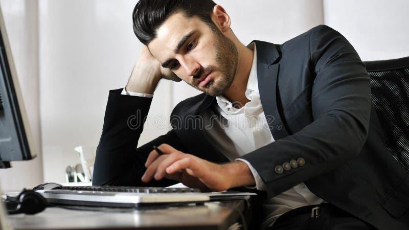 Утомленный пробуренный молодой бизнесмен в офисе стоковые фотографии rf