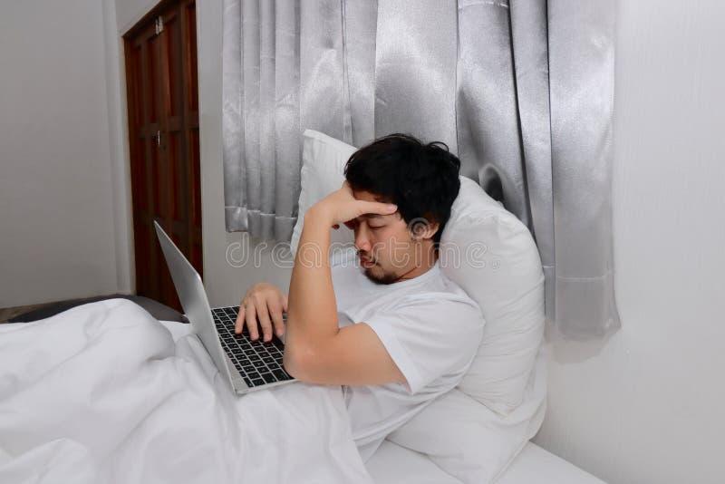Утомленный разочарованный азиатский человек с подушкой склонности компьтер-книжки на кровати в спальне Концепция перегрузки работ стоковые фотографии rf