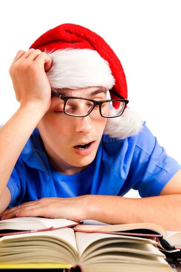 Утомленный студент в шляпе Санты стоковая фотография rf