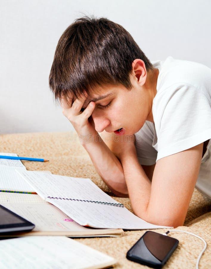 Утомленный студент делая домашнюю работу стоковые изображения rf
