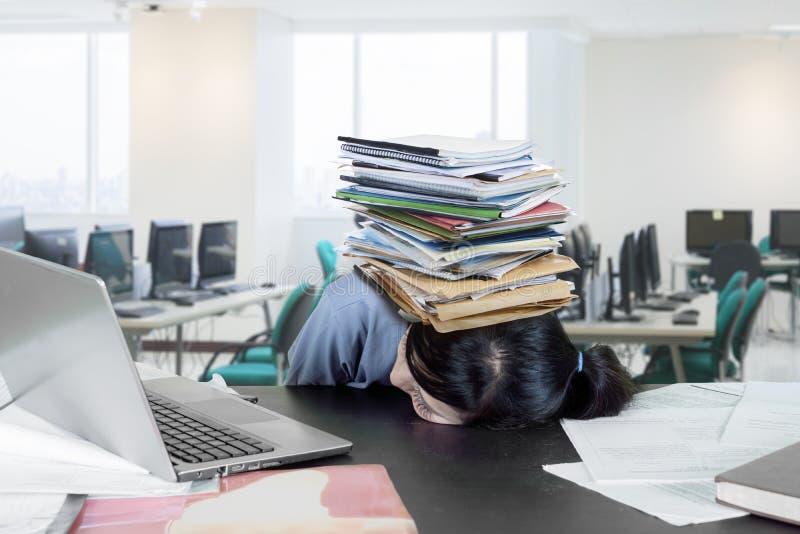 Утомленный студент колледжа с стогом книг стоковое изображение
